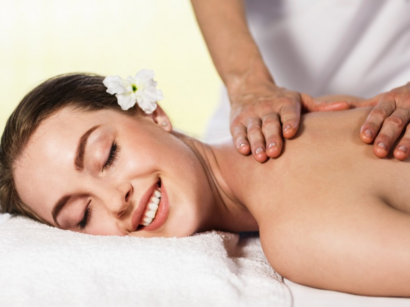 Portrait of a beautiful young woman lying on massage at spa center